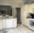 Large spacious kitchen with stainless steel appliances and gas stove.